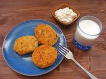 Rissoles ветчины, сыра и картошек на голубой плите, молока в стекле и сметаны в деревянном шаре на деревенской предпосылке с крыш Стоковая Фотография RF