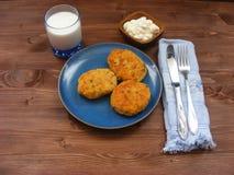 Rissoles ветчины, сыра и картошек на голубой плите, молока в стекле и сметаны в деревянном шаре на деревенской предпосылке с голу Стоковое Изображение
