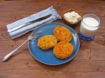Rissoles ветчины, сыра и картошек на голубой плите, молока в стекле и сметаны в деревянном шаре с голубыми салфеткой и крышкой Стоковые Изображения RF