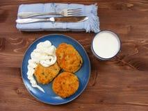 Rissoles ветчины, сыра и картошек на голубой плите, молока в стекле и сметаны в деревянном шаре на деревенской предпосылке с крыш Стоковое фото RF