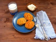 Rissoles ветчины, сыра и картошек на голубой плите, молока в стекле и сметаны в деревянном шаре на деревенской предпосылке с голу Стоковая Фотография
