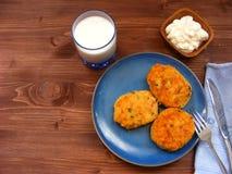 Rissoles ветчины, сыра и картошек на голубой плите, молока в стекле и сметаны в деревянном шаре на деревенской предпосылке Стоковые Изображения