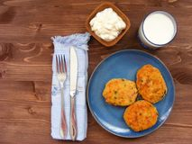 Rissoles ветчины, сыра и картошек на голубой плите, молока в стекле и сметаны в деревянном шаре на деревенской предпосылке с крыш Стоковая Фотография