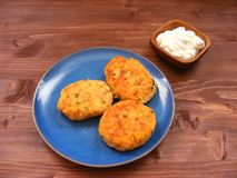 Rissoles ветчины, сыра и картошек на голубых плите и сметане в деревянном шаре на деревенской предпосылке Стоковое фото RF