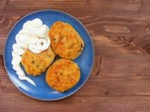 Rissoles ветчины, сыра и картошек с сметаной на голубой плите на деревенской деревянной предпосылке Стоковые Изображения
