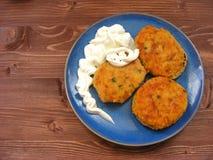 Rissoles ветчины, сыра и картошек с сметаной на голубой плите на деревянной предпосылке Стоковое Фото