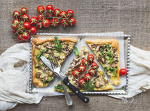 Ristic mushroom (fungi) square pizza with cherry tomatoes and ar. Ugula over a sackcloth background Stock Photos