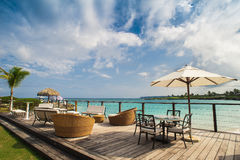 Ristorante all'aperto alla spiaggia. Caffè sulla spiaggia, sull'oceano e sul cielo. Regolazione della Tabella al ristorante tropic Fotografia Stock Libera da Diritti