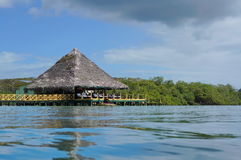 Ristorante caraibico sopra acqua con il tetto ricoperto di paglia immagini stock libere da diritti