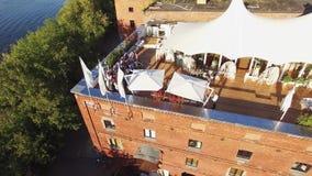 Ristorante del tiro di Quadrocopter sul tetto della costruzione di mattone a Mosca La cerimonia di nozze prende la foto stock footage