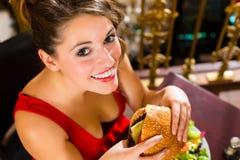 Ristorante della giovane donna in fine, mangia un hamburger Immagine Stock