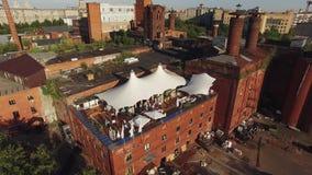 Ristorante di estate del tiro di Quadrocopter con le tende bianche sul tetto di vecchia costruzione nella città sunny La gente stock footage
