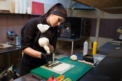 Ristorante di sushi dei iprepares del cuoco unico della donna nella cucina Immagine Stock Libera da Diritti