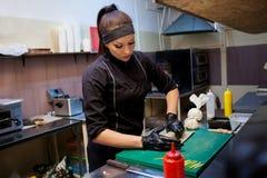 Ristorante di sushi dei iprepares del cuoco unico della donna nella cucina Fotografie Stock