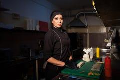 Ristorante di sushi dei iprepares del cuoco unico della donna nella cucina Fotografie Stock Libere da Diritti