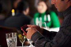 Ristorante: Testi dell'uomo sul telefono cellulare durante la cena Immagine Stock
