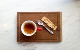 Ristreto kaffe Santa Claus med påsen av gåvorna kaffe i röd kopp med skeden och smällaren på träplattan Royaltyfria Foton