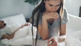 Risultato aspettante preoccupato del test di gravidanza della donna sul letto mentre sonno dell'uomo stock footage