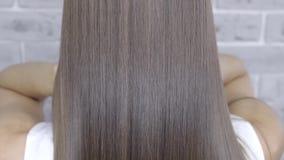 Risultato dopo laminazione e capelli che raddrizzano in un salone di bellezza per una ragazza con capelli marroni Concetto di cur video d archivio