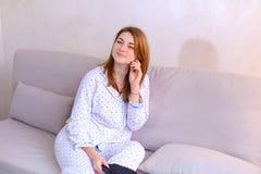 Risveglio della donna dopo il sogno nel buon umore in camera da letto sullo strato Fotografia Stock Libera da Diritti