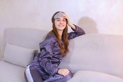 Risveglio della donna dopo il sogno nel buon umore in camera da letto sullo strato Fotografia Stock