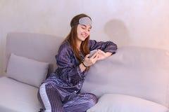 Risveglio della donna dopo il sogno nel buon umore con il cellulare a disposizione Fotografie Stock