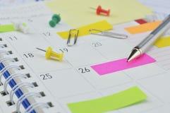 Rita med klibbiga anmärkningar och klämma fast på affärsdagboksidan Fotografering för Bildbyråer