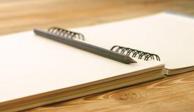 Rita på anteckningsboken med bokmärker som ligger på en trätabell Fotografering för Bildbyråer