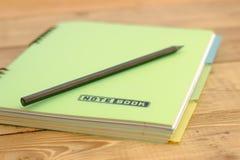 Rita på den stängda anteckningsboken med bokmärker som ligger på en trätabell Arkivbilder