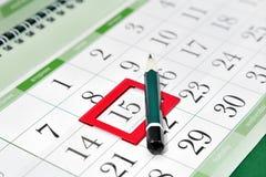 Rita på kalendern med en bokmärke på datumet Fotografering för Bildbyråer