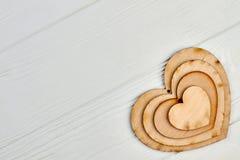 Ritagli di legno a forma di del cuore su legno leggero Fotografia Stock