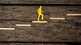 Ritaglio giallo della siluetta di una persona che scala le scale Fotografia Stock Libera da Diritti