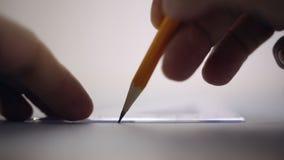 Ritaren drar en blyertspenna på ett ark av papper stock video