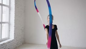 Ritmische gymnastiek: leuke tiener die een gymnastiekoefening met een gekleurd lint opleiden Mooie bevallig stock videobeelden
