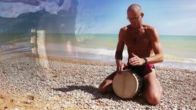 Ritmo da batida do jogador do cilindro de Djembe na praia só filme
