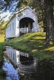 A reflection of Ritner Creek Covered Bridge in a pool of rainwater. stock image