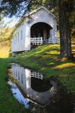 A reflection of Ritner Creek Covered Bridge in a pool of rainwater. stock images