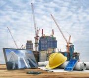 Ritningar och säkerhetshjälm i konstruktionsplats Arkivfoto
