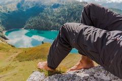 Ritom男性脚和腿有山的和湖的图象作为背景 免版税图库摄影