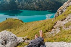 Ritom男性脚和腿有山的和湖的图象作为背景 免版税库存照片