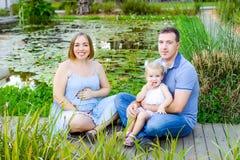 Ritratti di una famiglia di tre felice - moglie, padre e figlia incinti divertendosi vicino allo stagno con le ninfee nel parco f Fotografia Stock Libera da Diritti