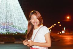 Ritratto abbastanza asiatico di notte della donna con il fondo leggero dei nuovi anni Immagini Stock