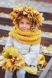 Ritratto adorabile sveglio della ragazza del bambino con il mazzo di camminata delle foglie e della corona di autunno all'aperto  Immagine Stock
