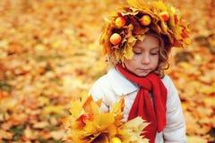 Ritratto adorabile sveglio della ragazza del bambino con il mazzo di camminata delle foglie e della corona di autunno all'aperto  Fotografia Stock