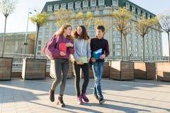 Ritratto all'aperto degli studenti adolescenti con gli zainhi che camminano e che parlano immagine stock libera da diritti