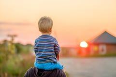 Ritratto all'aperto del figlio e del padre alla luce solare di tramonto Fotografia Stock