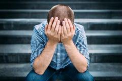 Ritratto all'aperto del giovane triste che copre il suo fronte di mani Fotografie Stock Libere da Diritti