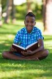 Ritratto all'aperto del ragazzo del nero dello studente che legge un libro Immagine Stock