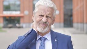 Ritratto all'aperto dell'uomo d'affari anziano con dolore al collo stock footage