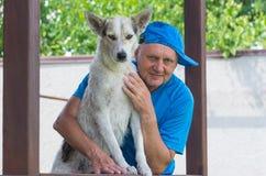 Ritratto all'aperto dell'uomo maturo felice e del suo giovane cane sveglio fotografia stock